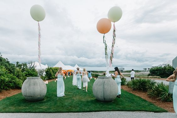 bridal-party-walking-towards-marquee-tent-three-tassel-balloons
