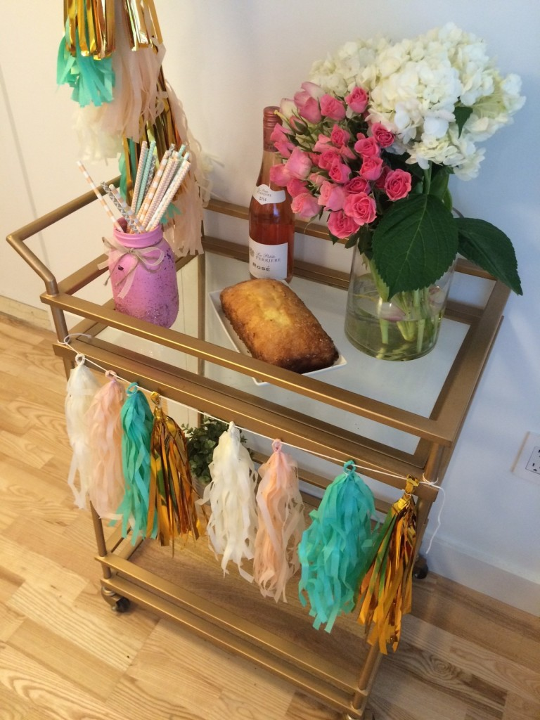 bar cart at a bridal shower with lemon bread, paper straws, rose, tassels and a huge bouquet