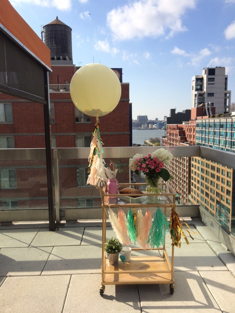 confetti balloon with tassels tied to a bar cart with hanging tassels by twigs and twirls