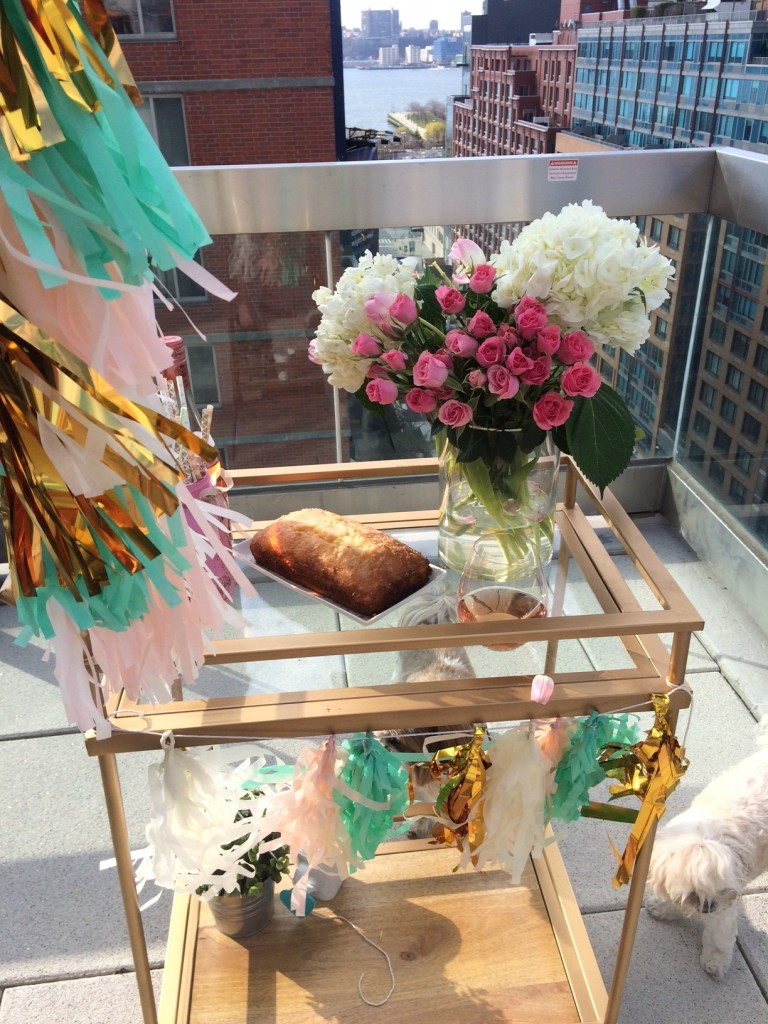 gold bar cart on rooftop with rose bouquet, lemon bread, rose champagne and a tassel balloon