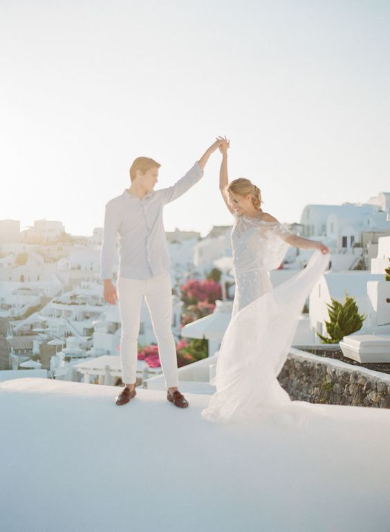 couple-in-white-dancing-in-santorini http://itgirlweddings.com/santorini-honeymoon-inspiration/
