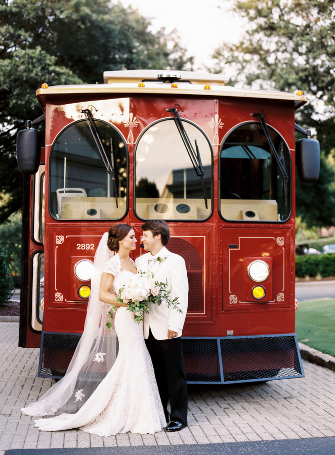 bride-groom-in-front-of-red-trolly http://itgirlweddings.com/southern-white-tie-wedding/