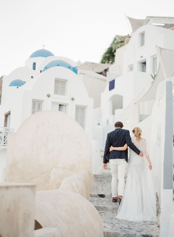 couple-walking-santorini-white-hillside http://itgirlweddings.com/santorini-honeymoon-inspiration/