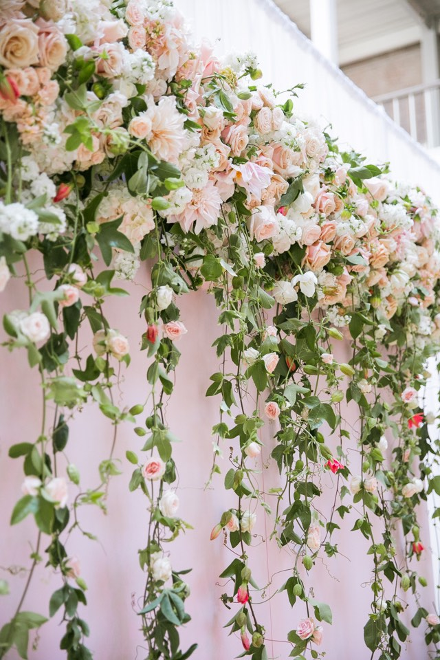 hanging-pink-roses-on-pink-wall-wedding-ceremony-backdrop http://itgirlweddings.com/write-wedding-vows/