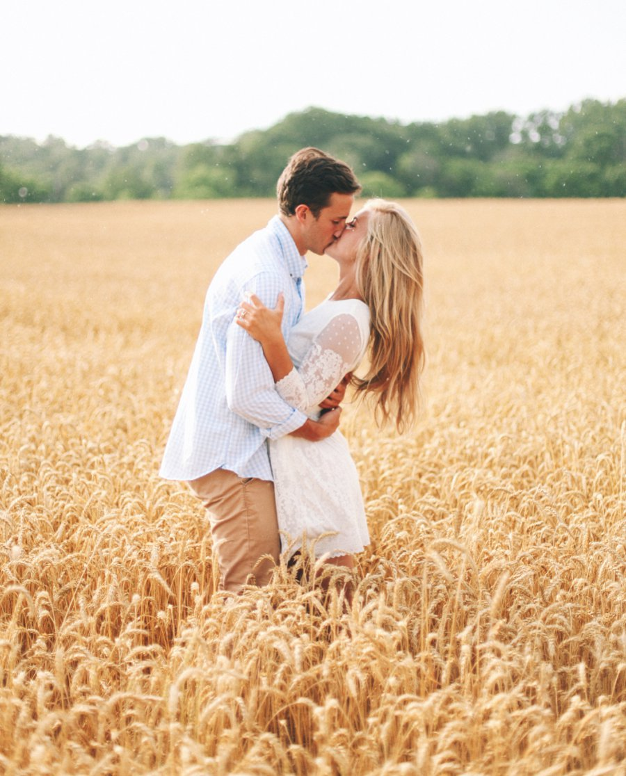kissing-in-a-field http://itgirlweddings.com/how-one-couple-nailed-their-engagement-session/