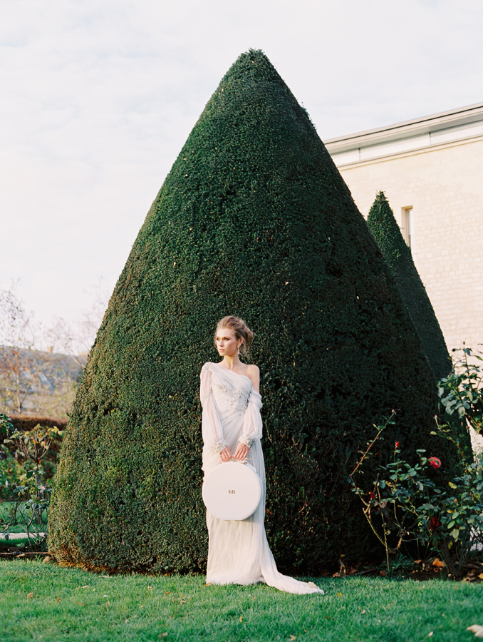 bride-standing-in-front-of-hedges-holding-hat-box http://itgirlweddings.com/parisian-wedding-inspiration/