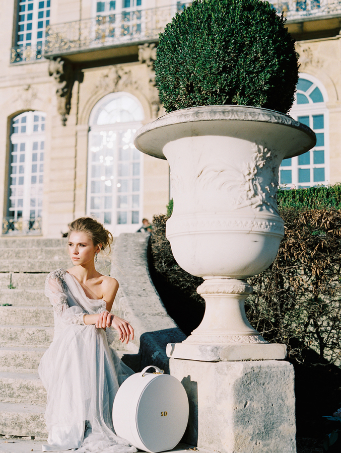 bride-on-the-steps-of-Musee-Rodin-with-hat-box http://itgirlweddings.com/parisian-wedding-inspiration/