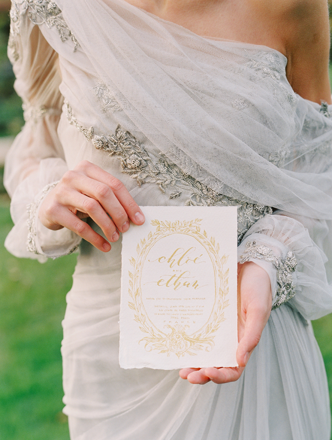 bride-holding-custom-gold-invitations http://itgirlweddings.com/parisian-wedding-inspiration/