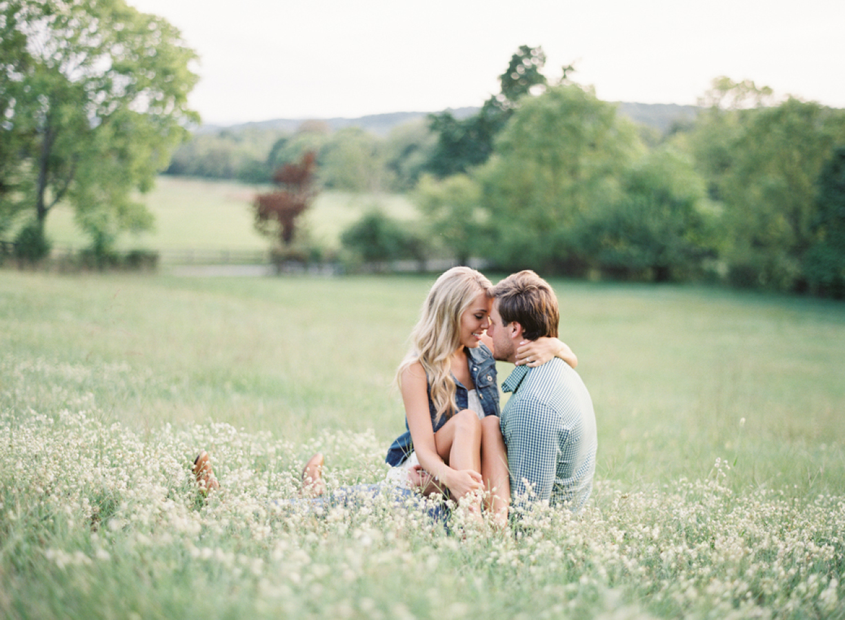 couple sitting in a field http://itgirlweddings.com/wedding-planning-timeline/