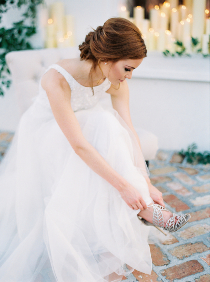 bride trying on wedding shoes http://itgirlweddings.com/timeless-traditional-style/