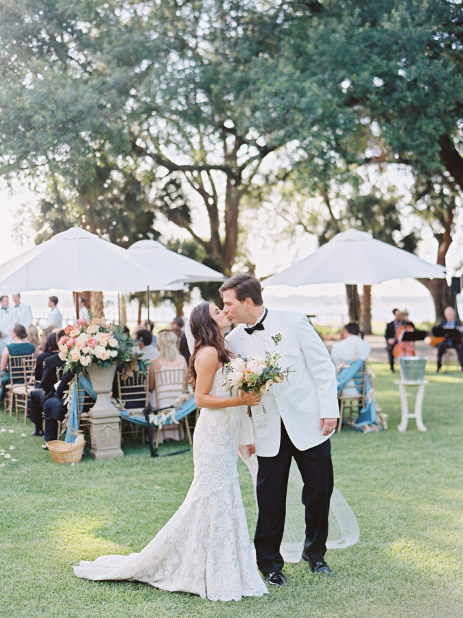 bride and groom kiss after ceremony http://itgirlweddings.com/southern-wedding-with-a-surprise-grand-exit/