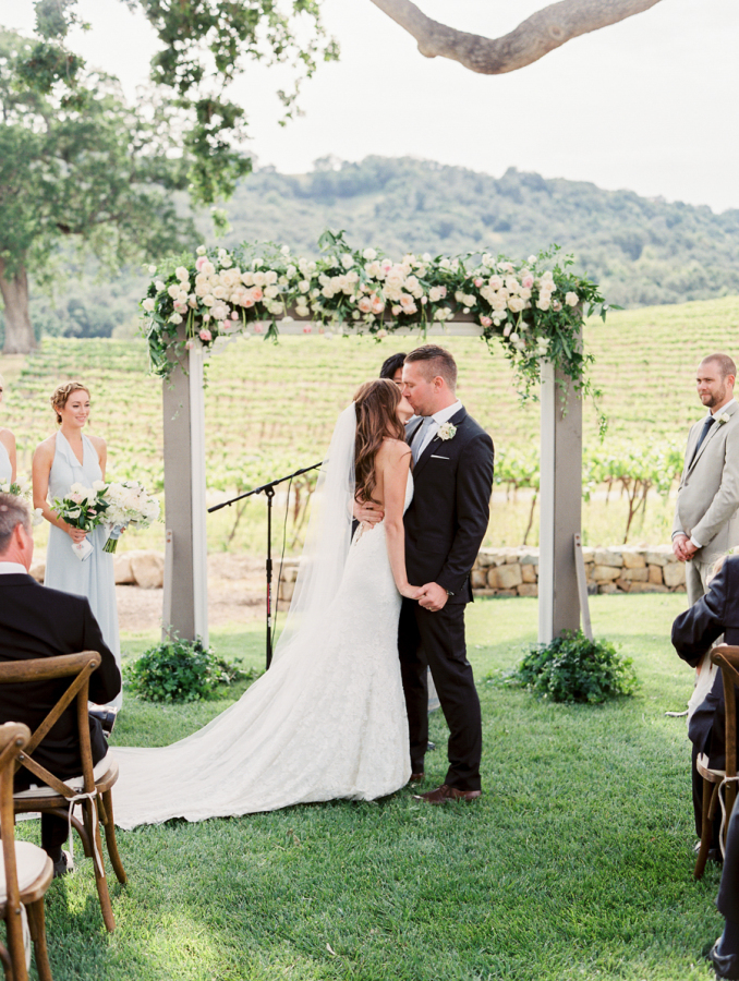 bride and groom ceremony kiss http://itgirlweddings.com/pretty-vineyard-wedding/