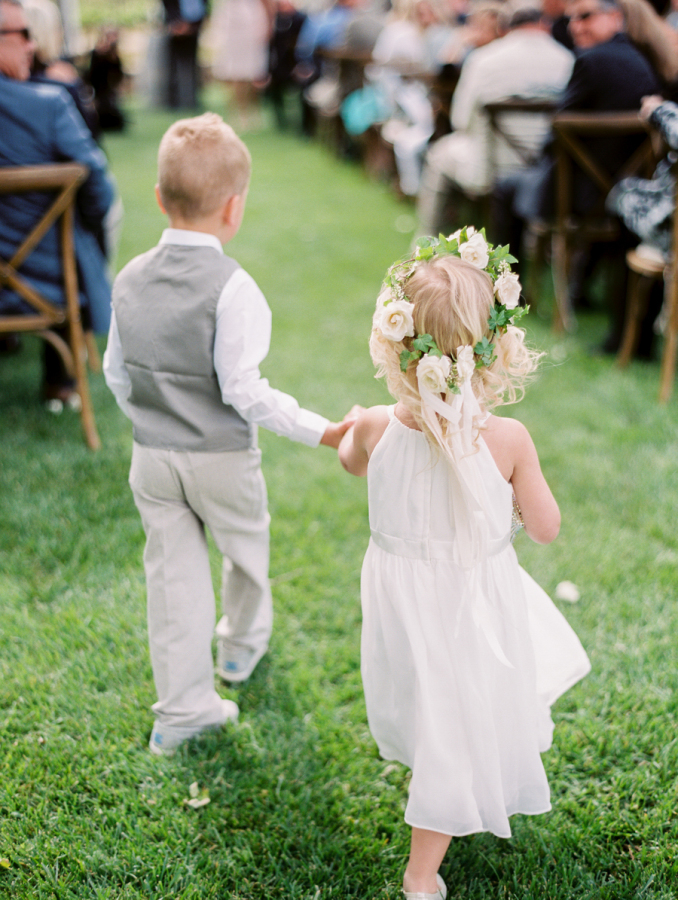 ring bearer and flower girl holding hands http://itgirlweddings.com/pretty-vineyard-wedding/