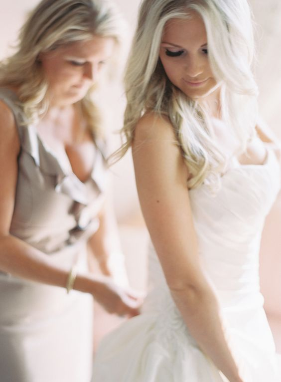 mother of the bride putting on dress http://itgirlweddings.com/who-is-responsible-for-what-on-your-wedding-day/