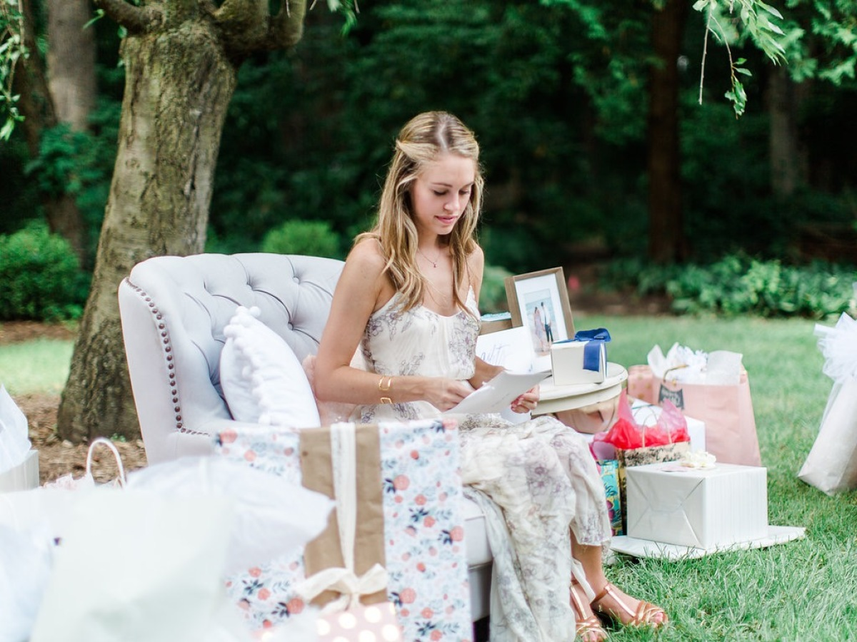 bride opening bridal shower gifts http://itgirlweddings.com/garden-bridal-shower/