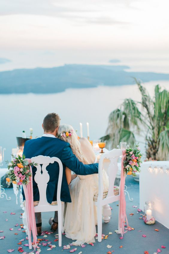 couple at table overlooking ocean on honeymoon