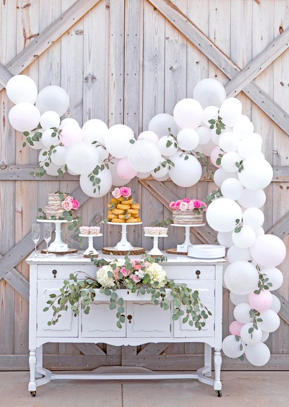 bridal shower dessert table with balloons and greenery