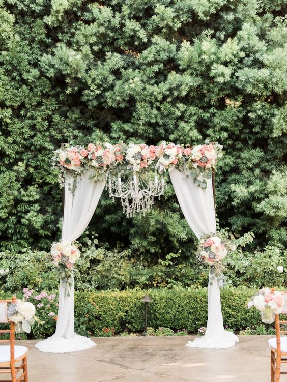 pink and white flowers on wedding arbor