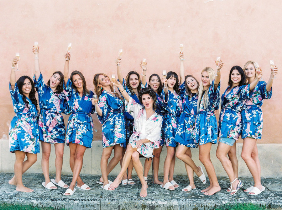 bridesmaids in blue floral robes with champagne
