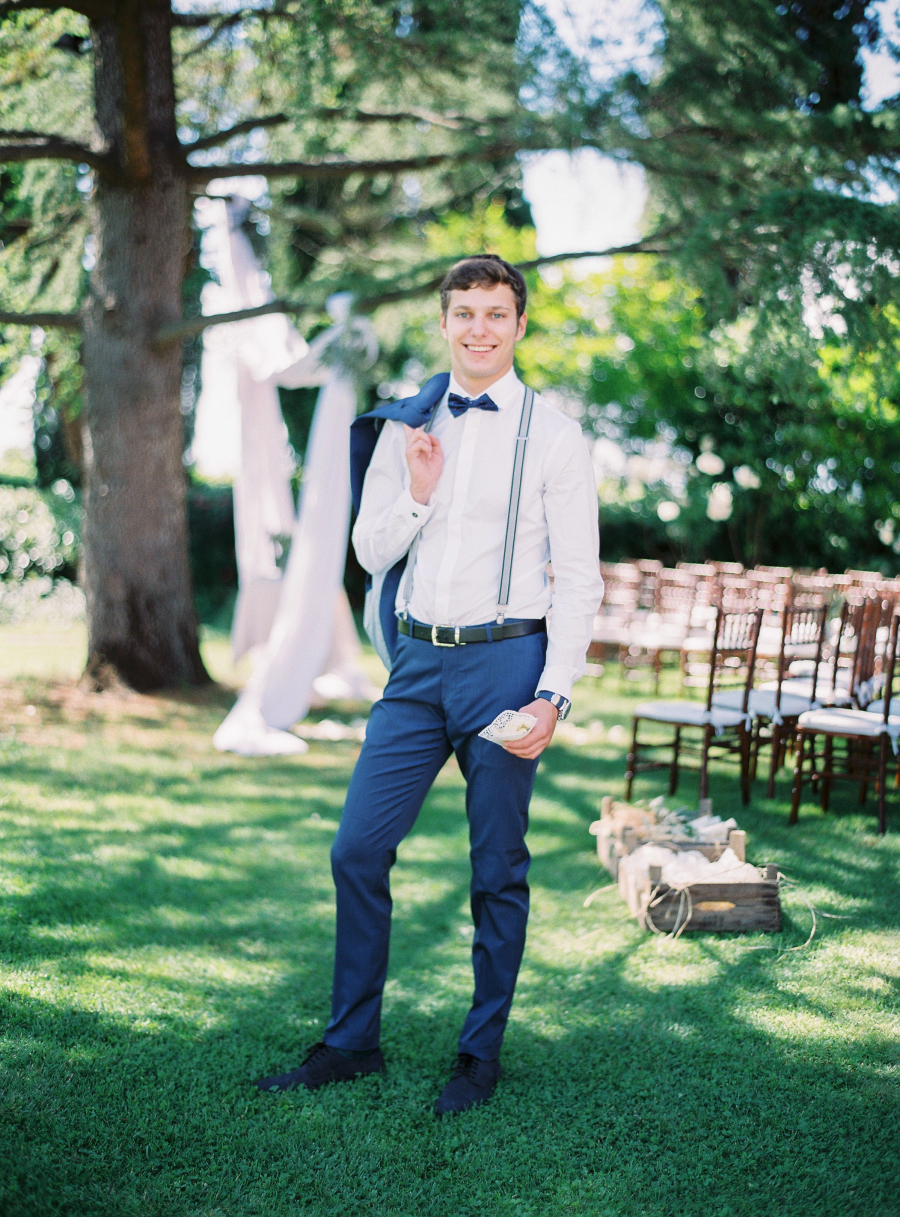 groom in navy and suspenders