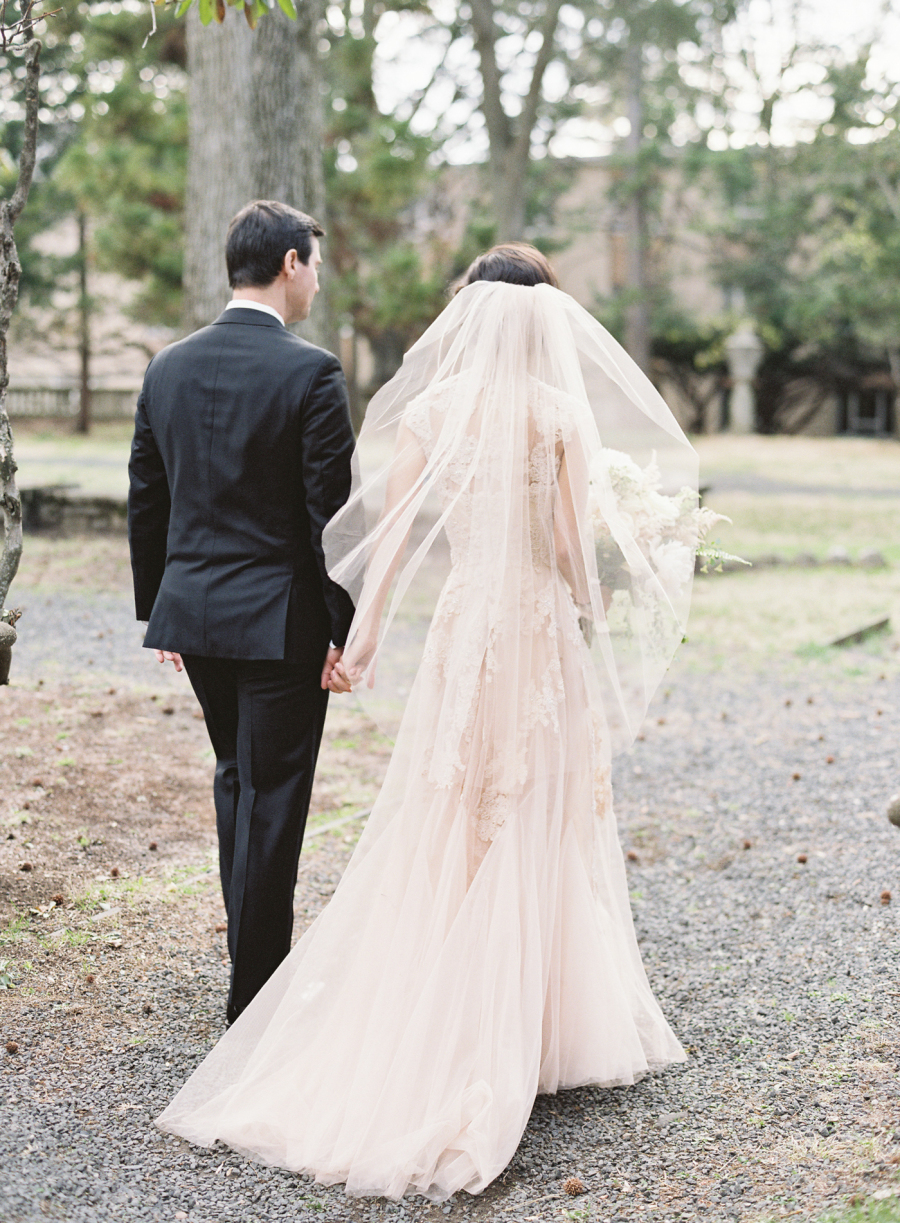 bride and groom back pose with veil