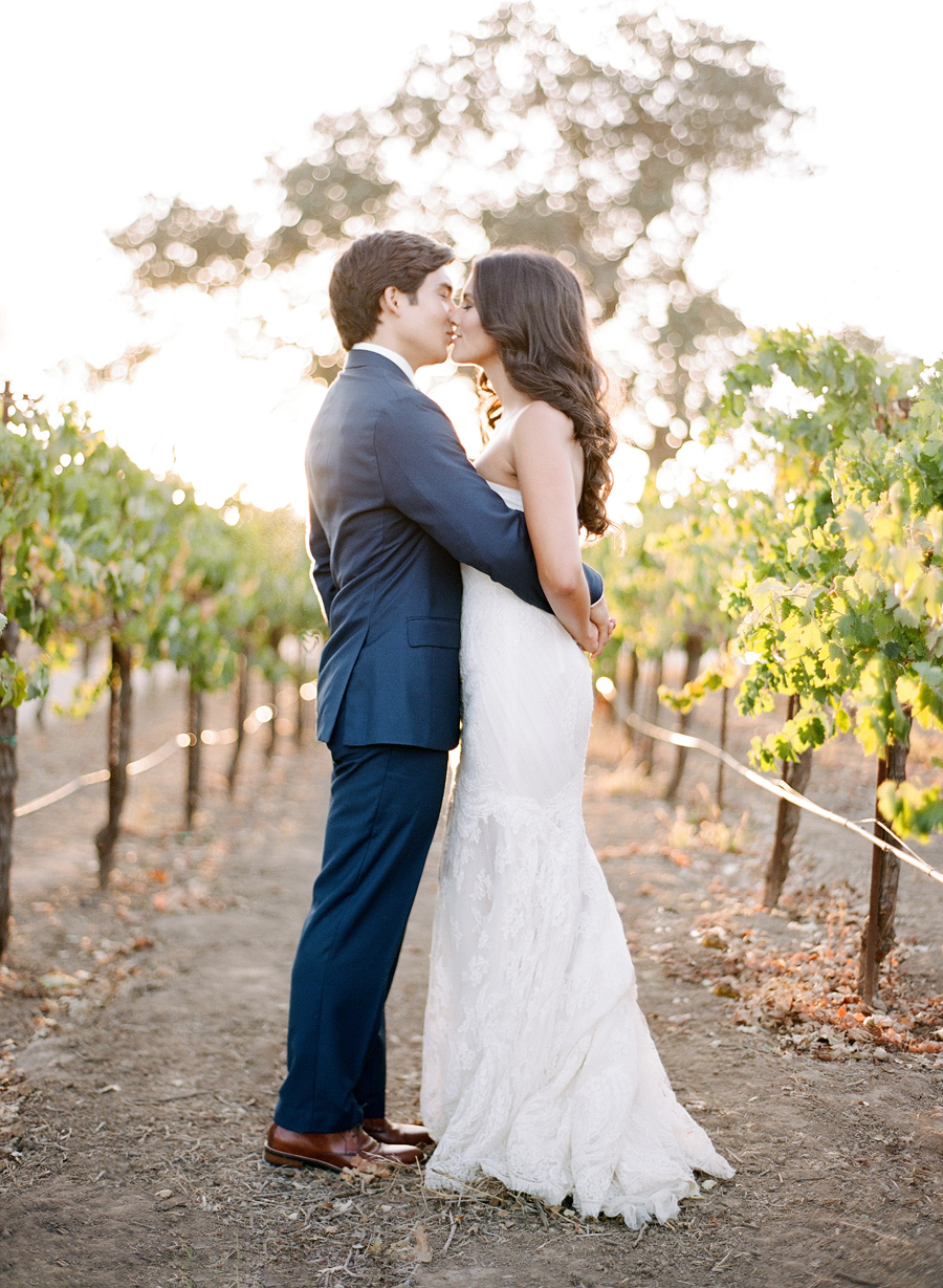 bride and groom kiss on a vineyard