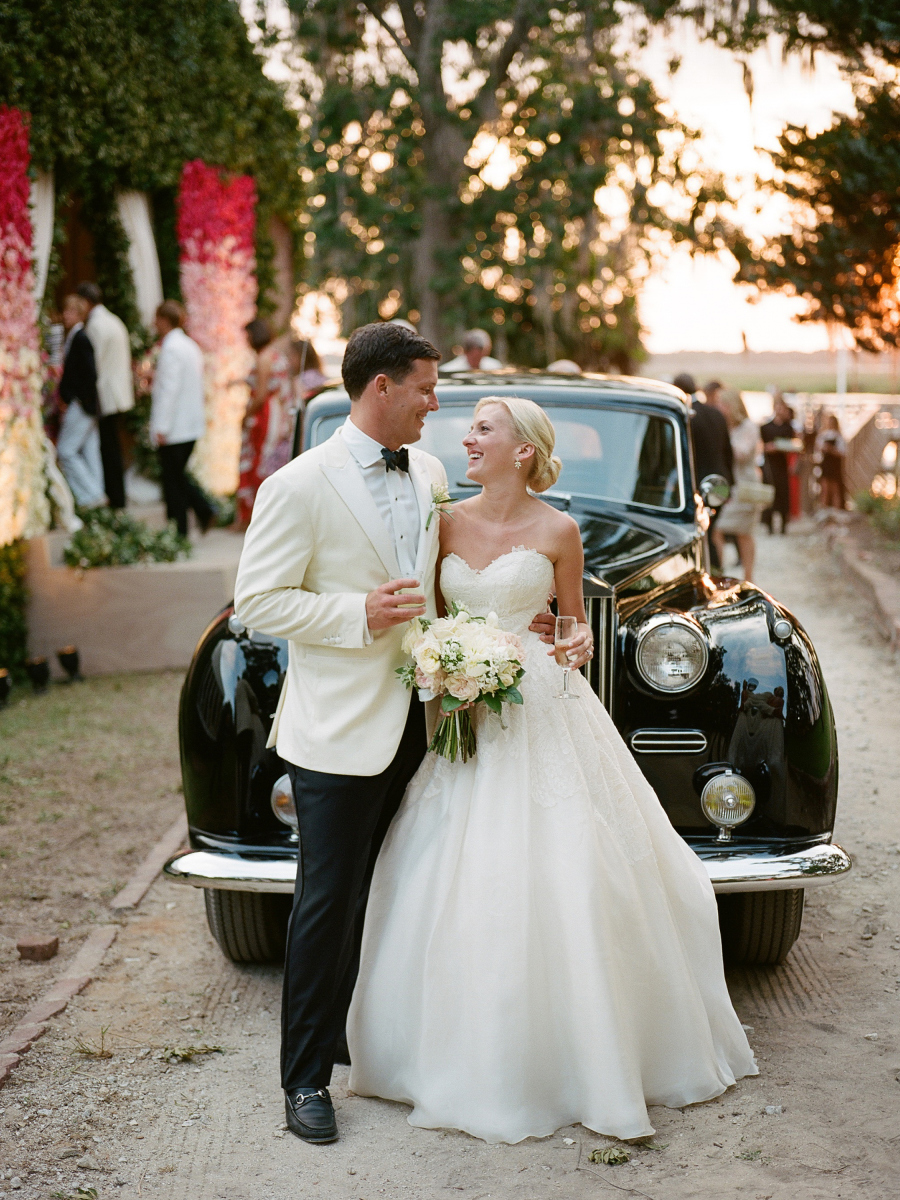 bride and groom toasting in front of vintage car
