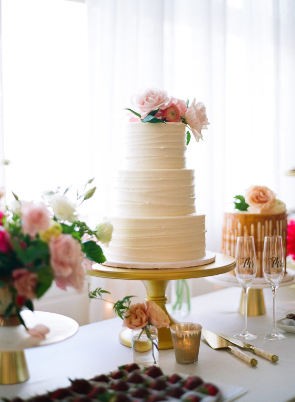 white wedding cake with pink florals on top