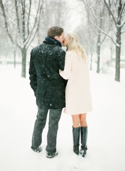 engaged couple kissing in the snow | It Girl Weddings
