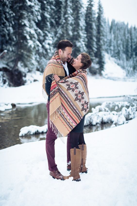 engagement session in the show hugging with poncho | It Girl Weddings