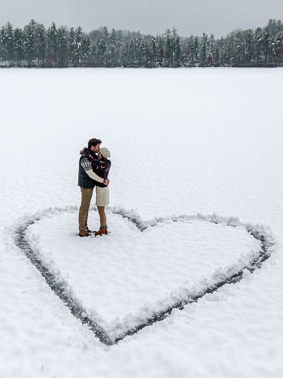 couple hugging in large heart in the snow | It Girl Weddings