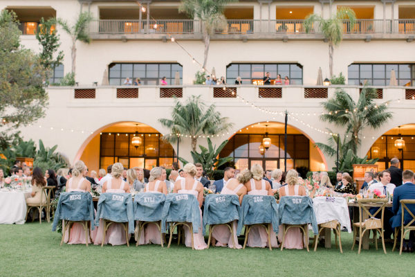 denim jackets hanging on back of bridesmaids reception chairs
