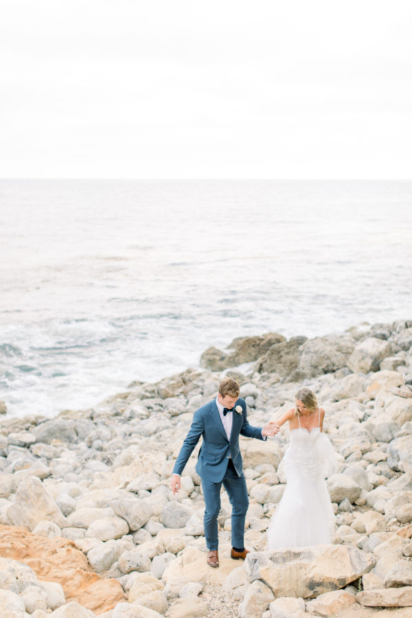 groom and bride walking on rocky beach