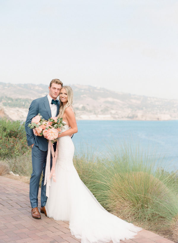 groom and bride formal pose with ocean view
