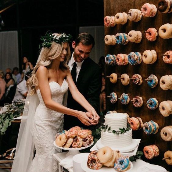 bride and groom next to donut wall