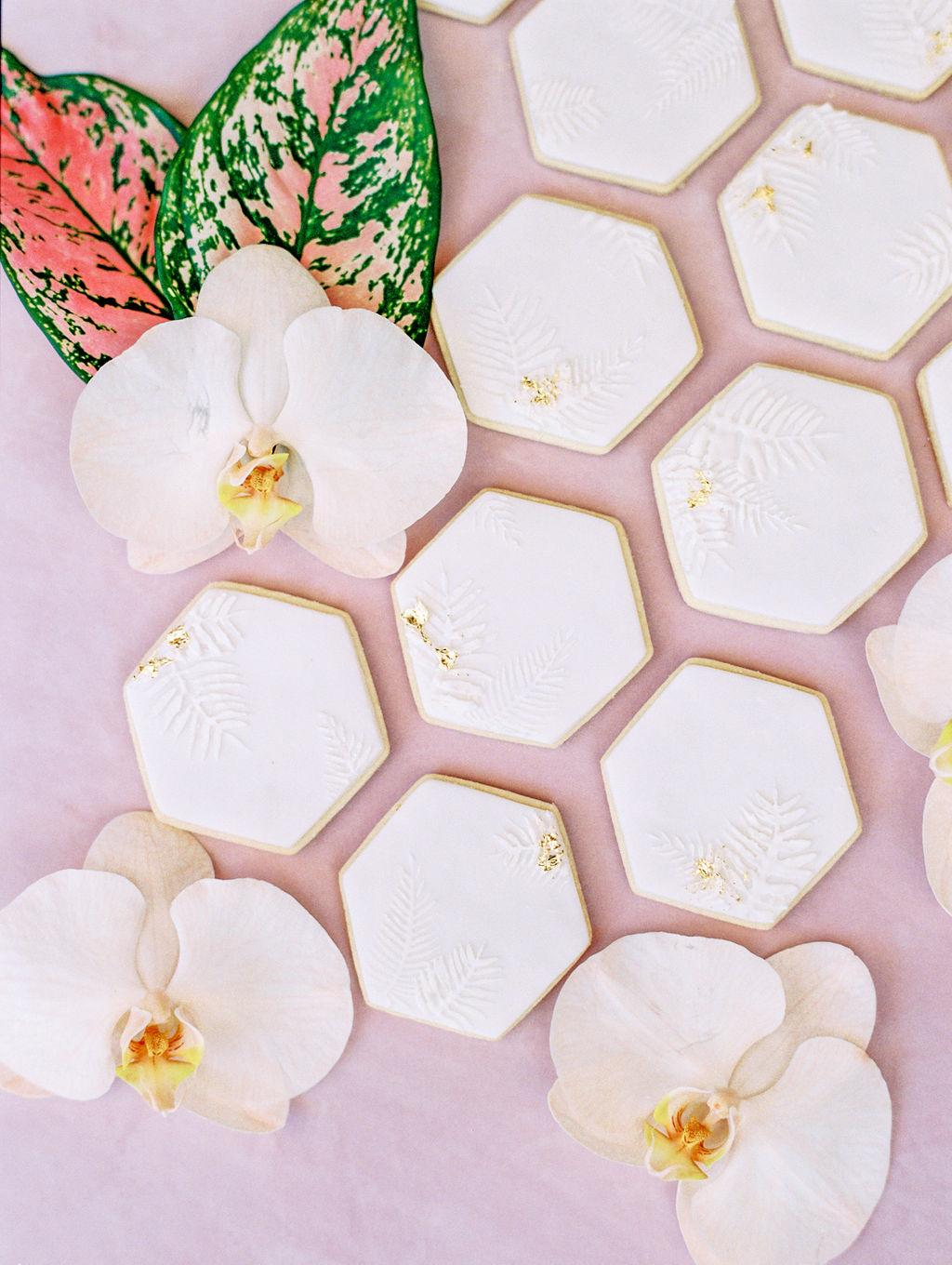 white tropical cookies with a touch of gold https://itgirlweddings.com/styled-shoot-with-pink-tropical-wedding-vibes/