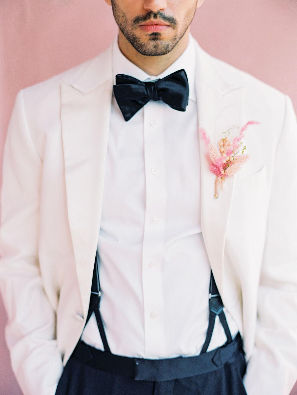 white groom tux with black bow toe and pink boutonniere https://shopstyle.it/l/bhio8